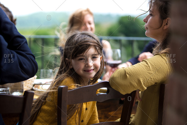 Portrait of girl at a family meal outdoors