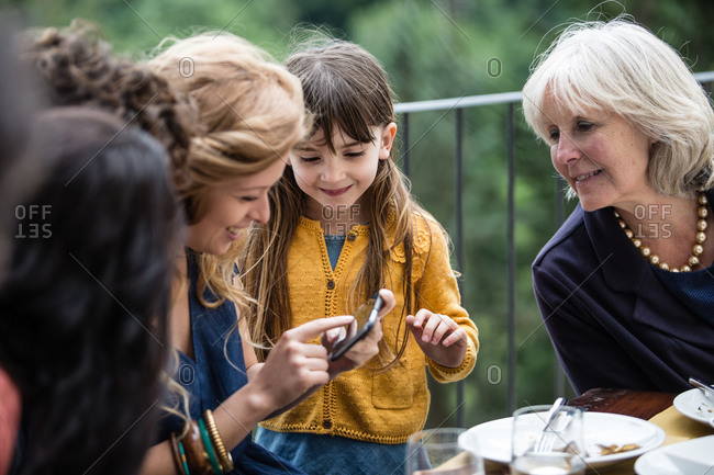 Generations of family all looking at smartphone together