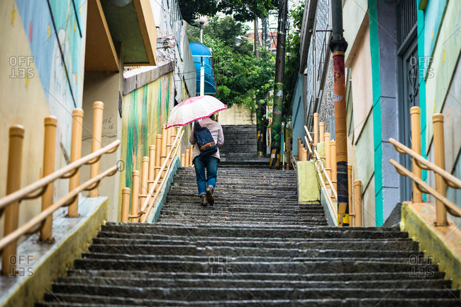 Busan, Korea - May 24, 2016: Person walking up a long stairway on a rainy street in Busan, South Korea