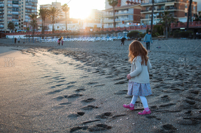 Girl walking on a beach at sunset in Spain