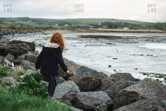 Red hair girl in a coat walking on the seashore in Ireland
