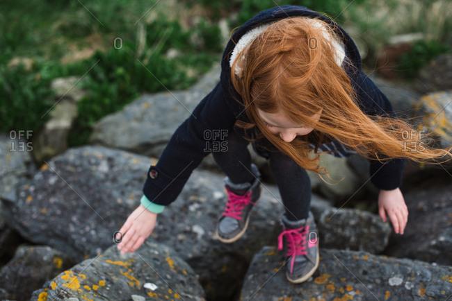 Red hair girl in a coat walking on rocks on the seashore in Ireland