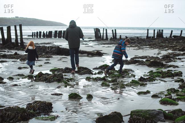 Family in coats walking on a beach in Ireland