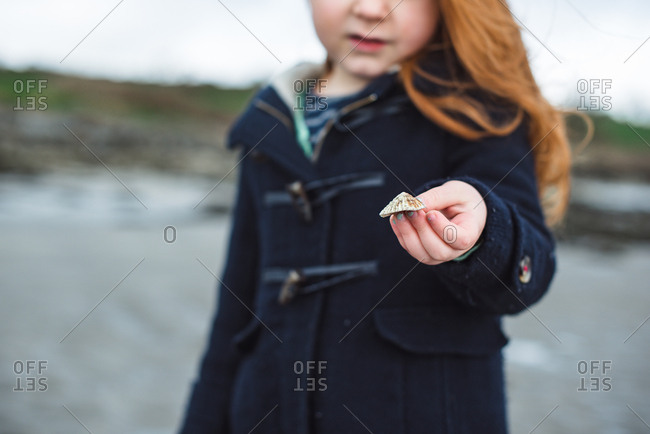 Girl on the beach showing a shell in her hands