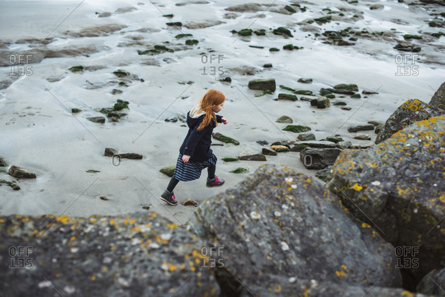 View from above of red hair girl in coat walking on the beach at seashore in Ireland