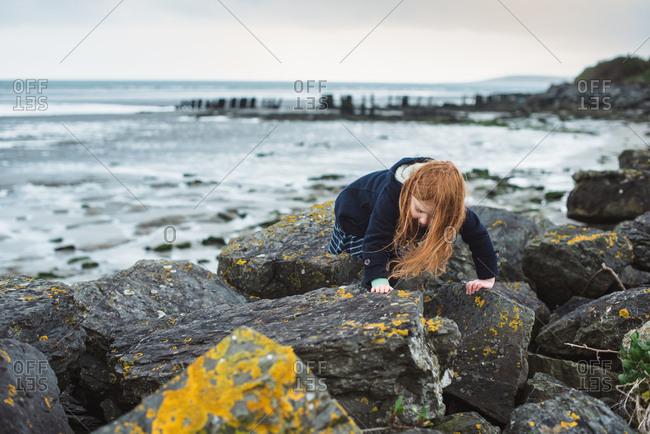 Red hair girl in coat walking on rocks at seashore in Ireland