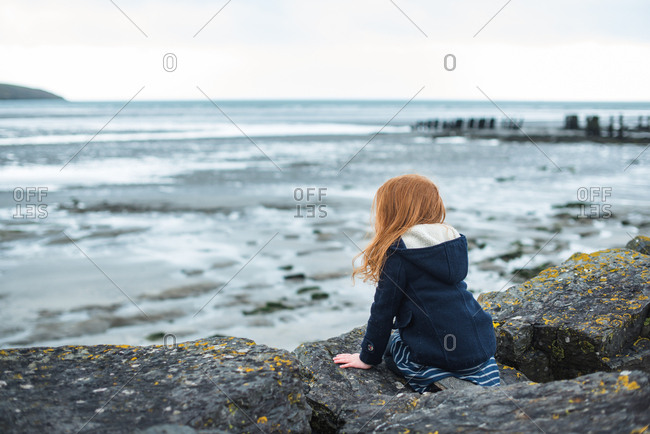 Red hair girl in coat sitting on rocks and watching the sea at seashore in Ireland
