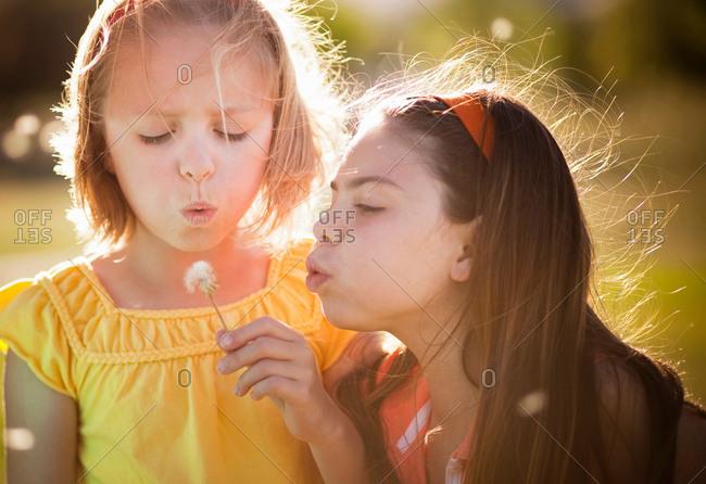 2 girls blowing on dandelion