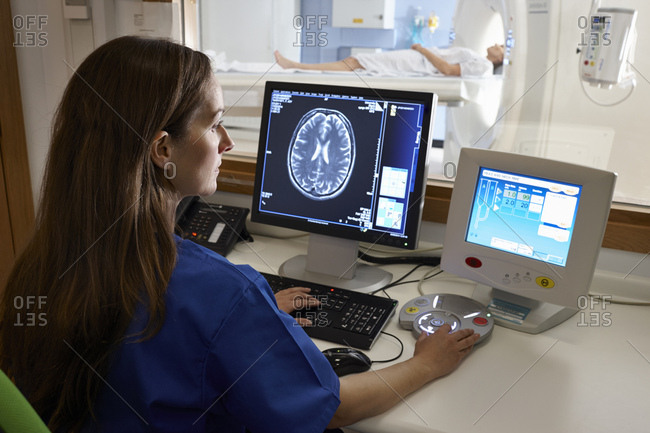 Radiologist looking at brain scan image on computer screen