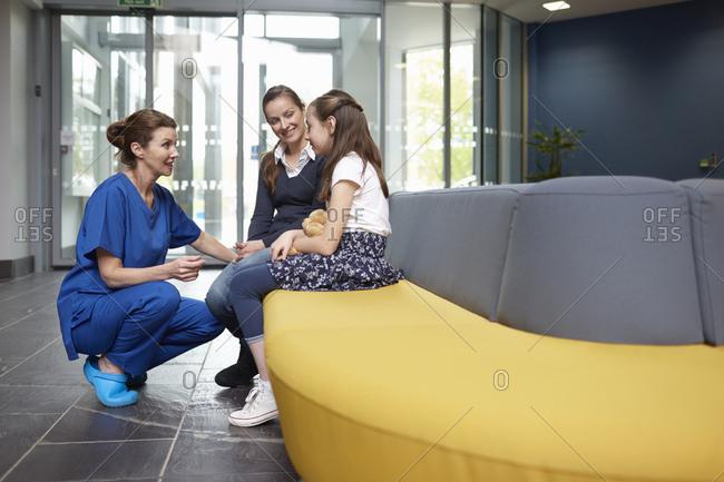 Nurse speaking to girl in hospital waiting room