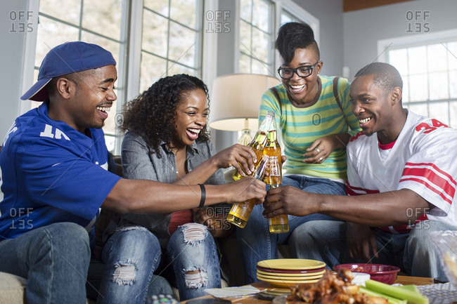 Four adult friends toasting with bottled beer on living room sofa