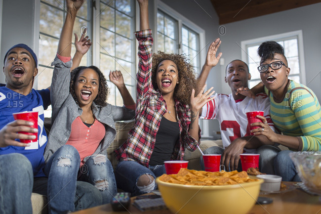 Five adult friends celebrating whilst watching TV from sofa