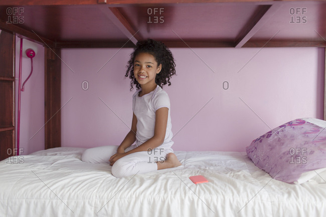 Girl wearing pyjamas kneeling on bed, looking at camera smiling