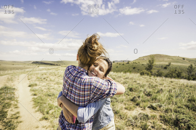 Two young women hugging each other on dirt track, Bridger, Montana, USA