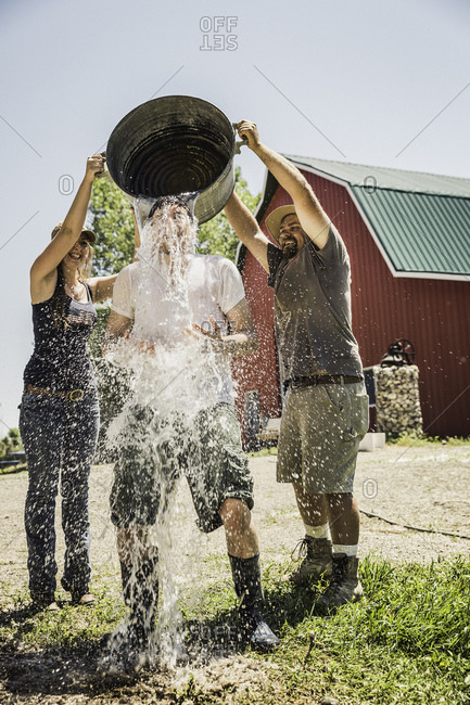 Farmworkers pouring water from metal bucket on friend
