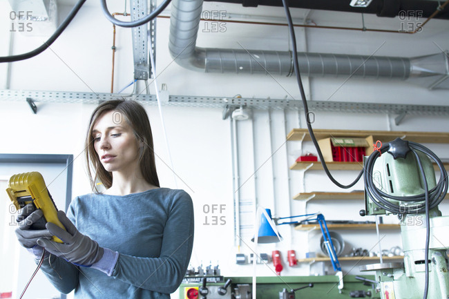 Woman wearing latex gloves looking at machine control panel in workshop