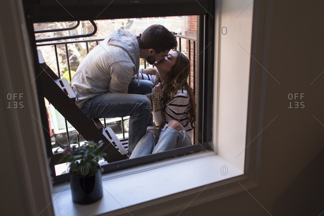 Young couple sitting on fire escape, kissing