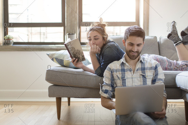 Young couple relaxing at home, young woman reading book, young man using laptop