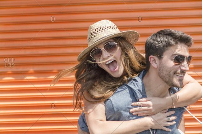 Man giving friend piggyback, Coney island, Brooklyn, New York, USA