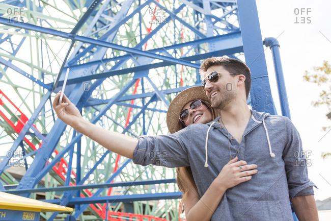 Couple at fairground using smartphone to take selfie, Coney island, Brooklyn, New York, USA
