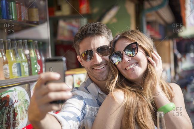 Couple using smartphone to take selfie, Coney island, Brooklyn, New York, USA