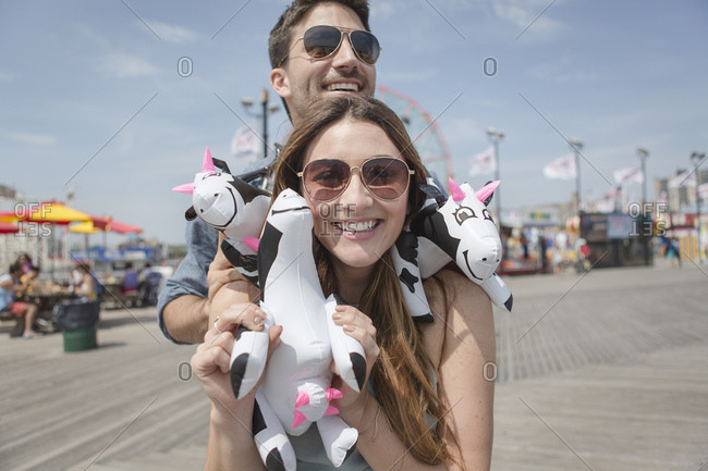 Couple holding cuddly toy cows smiling, Coney island, Brooklyn, New York, USA