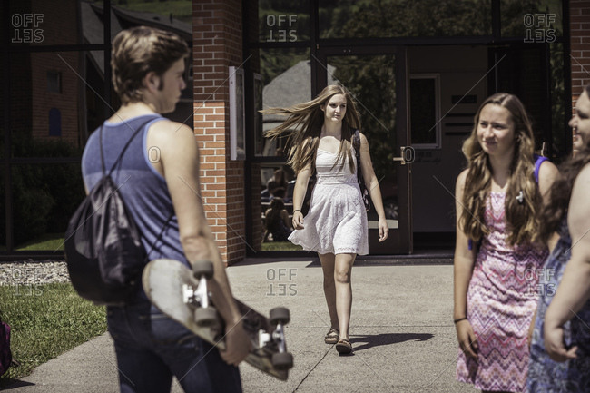Male and female high school students arriving and leaving high school