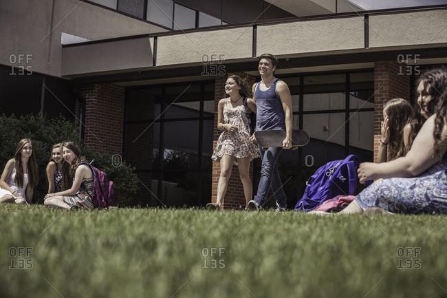 Teenage high school couple leaving high school together