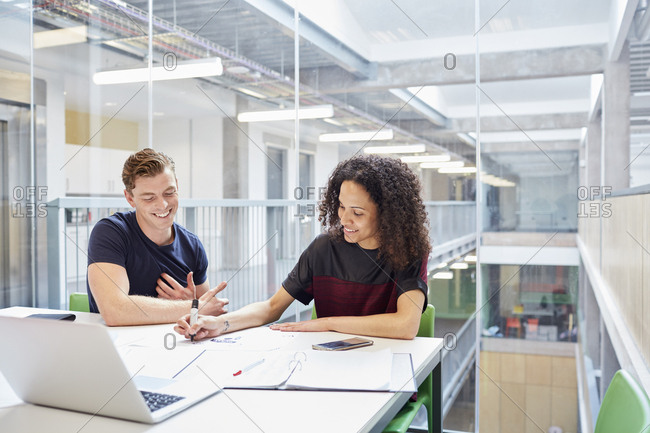Male and female designers brainstorming in design studio