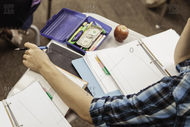 Cropped shot of teenage boy at desk with notebooks and files in high school lesson