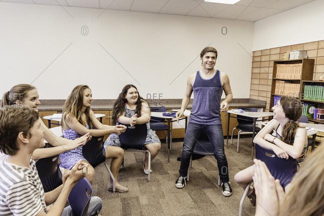 Teenage boy applauded by high school students in dance class
