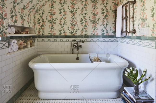 January 2, 2015 - Los Angeles, California: Vintage bathtub in beautiful floral wallpapered bathroom