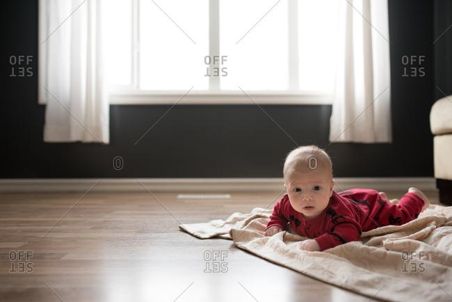Baby lying on blanket on the floor