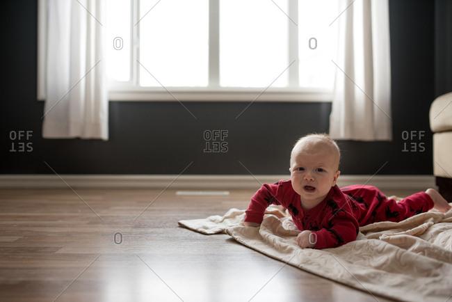 Upset baby lying on a floor