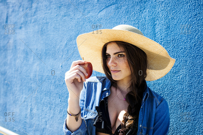 Woman in sun hat with apple next to blue wall