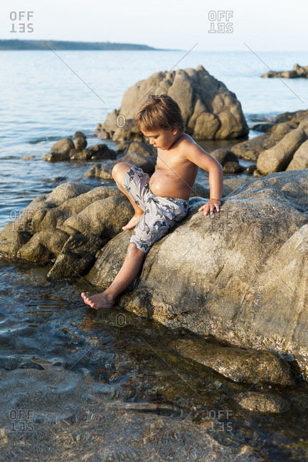 Little boy climbing on rocks in the ocean