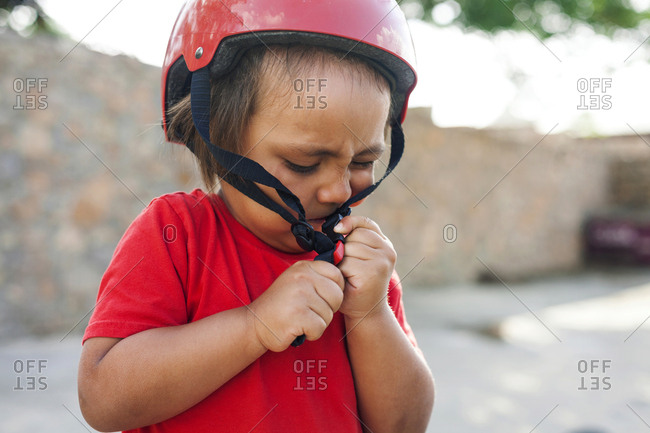 Toddler boy struggles with bike helmet