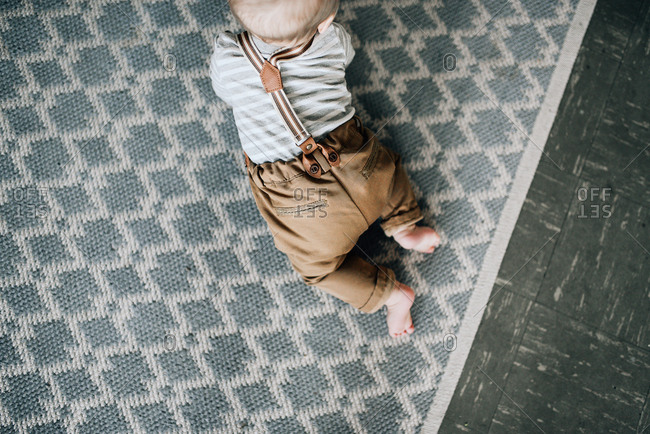 Baby in suspenders crawling on floor