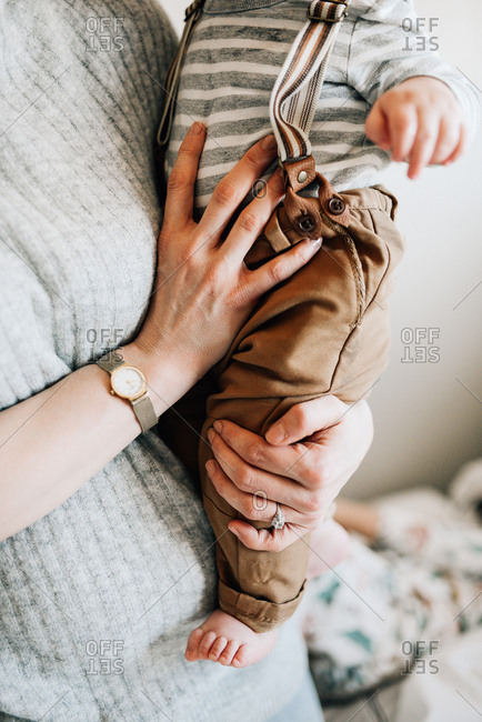 Woman holding baby boy in suspenders