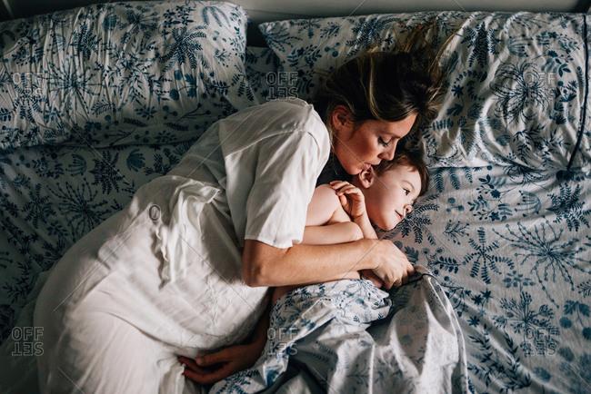 Pregnant woman cuddling boy
