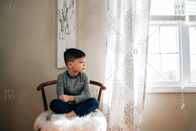 Reflective boy sitting near window