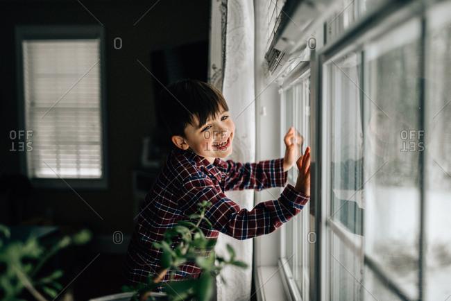 Happy boy looking out window