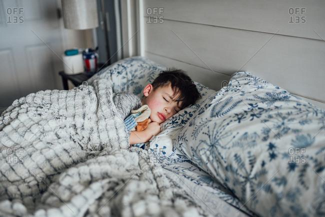 Boy sleeping in bed in sunlight