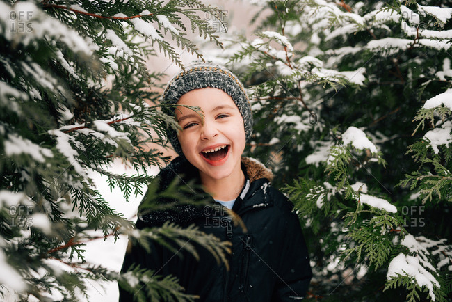 Laughing boy between snowy trees