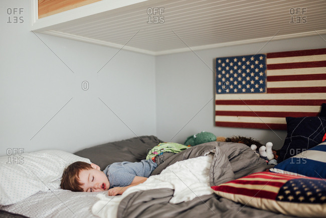 Boy sleeping near American flag decorations