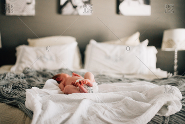 Baby with bare feet napping on bed
