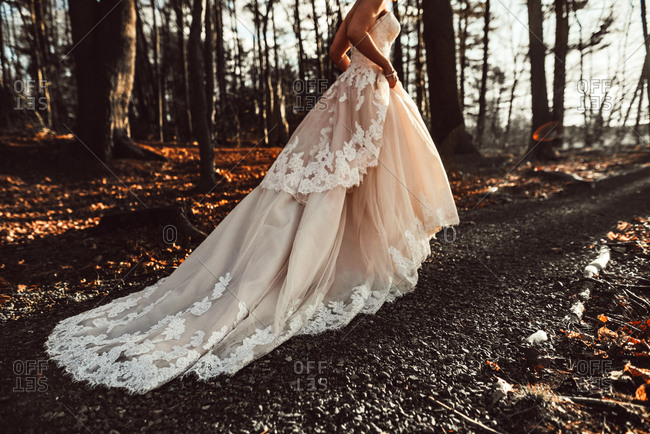 Woman in lace wedding dress in woods