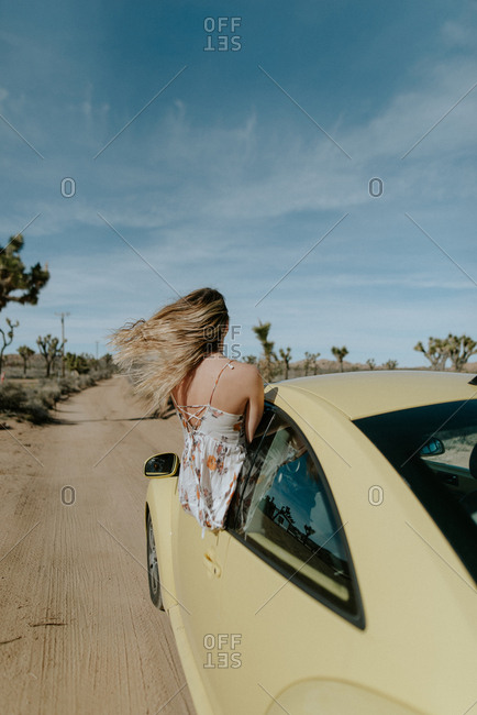 Woman leaning out the window of her car in desert