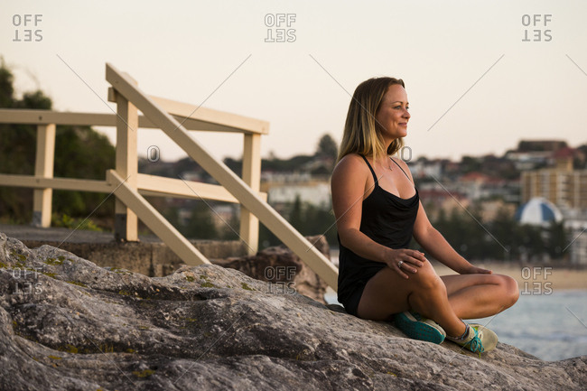 Woman sitting on rocks on beach at dusk
