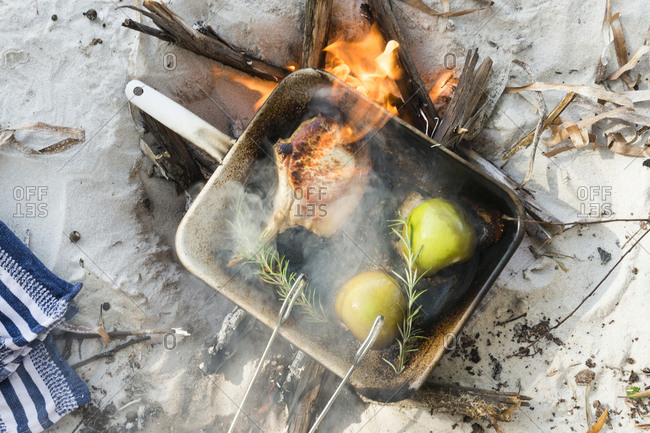 Flaming pork chop being cooked with apples and rosemary on beach campfire